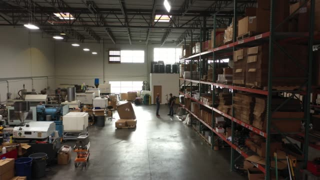 vídeos de stock e filmes b-roll de american manufacturing factory injection molding machines and warehouse shelves - armazém