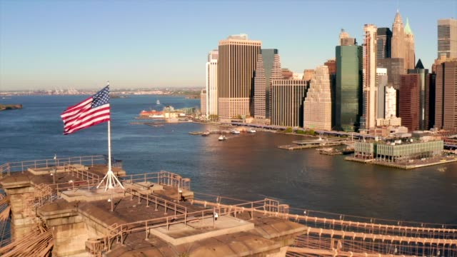 American national flag on sunny morning American national flag on sunny morning on top of the Brooklyn bridge with New York city Manhattan island in the background. east stock videos & royalty-free footage