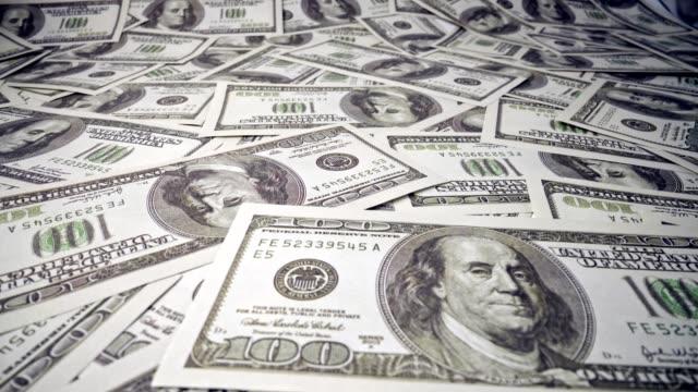 vidéos et rushes de pile américaine de billet de banque de papier de cent dollars sur le bureau. - tirelire