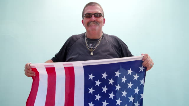 American Patriot posing and hiding behind flag Senior American man with sunglasses showing American flag, isolated on blue wall background veteran stock videos & royalty-free footage