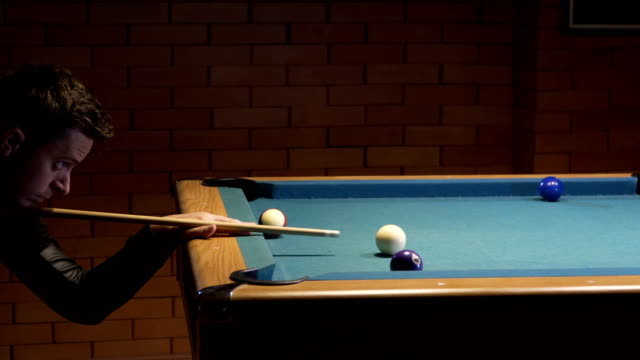 american pool, young man is aiming to hit the cue ball - campionato video stock e b–roll