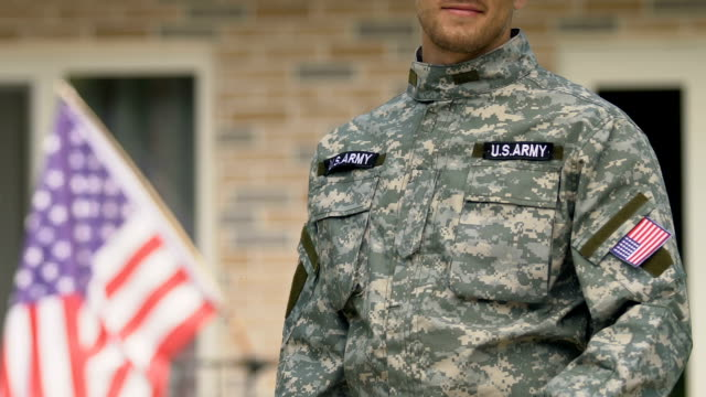 American soldier showing house key standing outside building, real estate owner