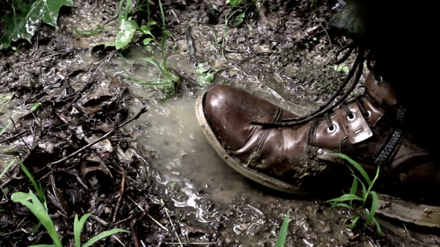 vídeos de stock e filmes b-roll de american soldier's boot steps in the mud in the jungle - bota