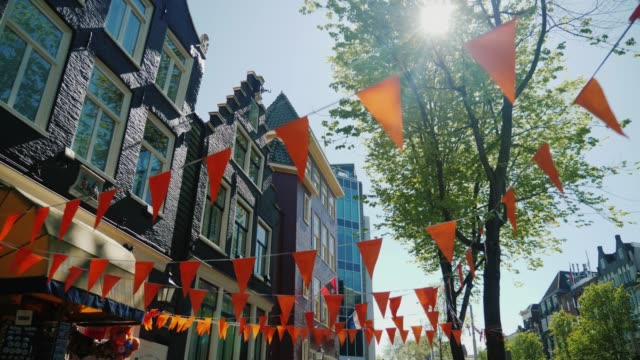 amesterdam, netherlands, may 2018: walking in the streets of amsterdam. old houses and triangular orange flags at the top. steadicam pov video, low angle shot - amsterdam video stock e b–roll