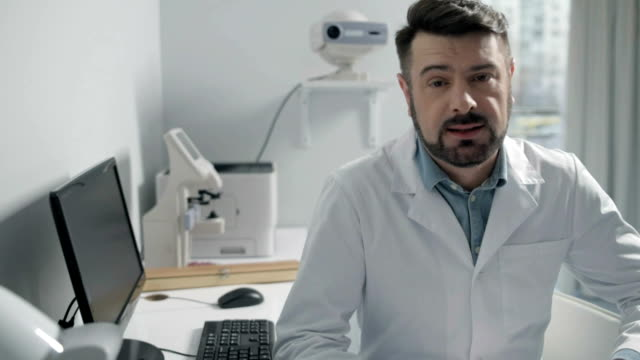 Amiable doctor giving talk in office Experienced medical specialist. Bearded male medical professional talking about something while sitting at a table in a private clinic camera photographic equipment stock videos & royalty-free footage