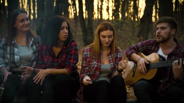 Amiable tourists by campfire singing songs with guitar in dark forest video