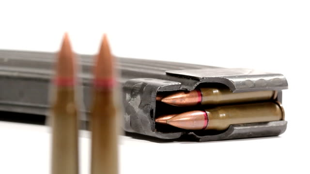AK-47 ammunition. Defocus from a laying full magazine in the back to two upright bullets in the front. video