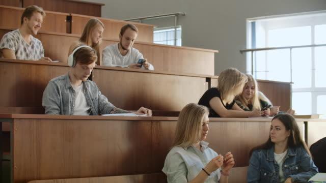 unter einer großen gruppe von studenten im publikum hört ein mann musik. hören sie musik und entspannen sie sich. hören - vorlesungsfrei stock-videos und b-roll-filmmaterial
