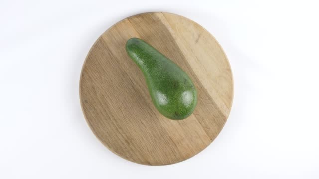 Amount of calories in avocado, male hand puts a plate with the number of calories on a avocado, top shot 60 fps video