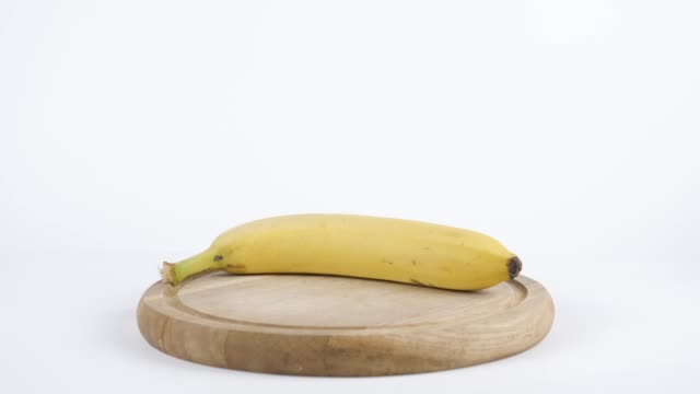 Amount of calories in banana, male hand puts a plate with the number of calories on a banana, healthy nutrition concept 60 fps video