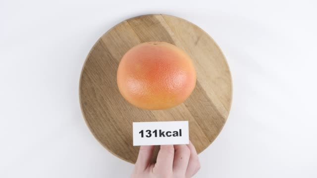 Amount of calories in grapefruit, male hand puts a plate with the number of calories on a grapefruit, top shot 60 fps video