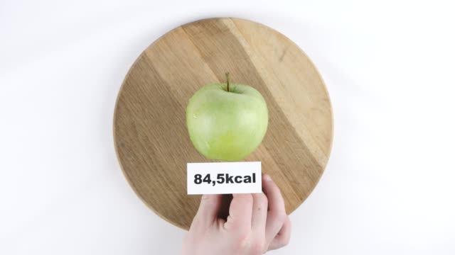 Amount of calories in green apple, male hand puts a plate with the number of calories on a green apple, top shot 60 fps video