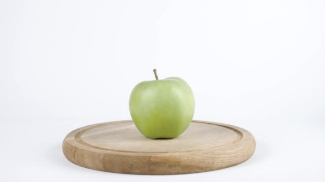 Amount of calories in green apple, male hand puts a plate with the number of calories on a green apple, healthy nutrition concept 60 fps video