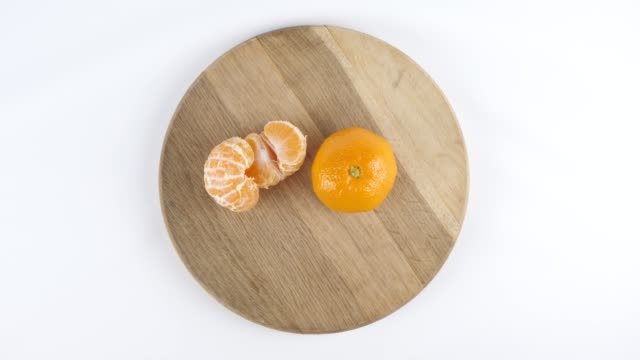 Amount of calories in Mandarin, male hand puts a plate with the number of calories on a Mandarin, top shot video