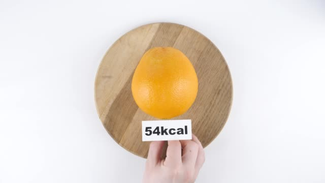 Amount of calories in orange, male hand puts a plate with the number of calories on a orange, top shot 60 fps video