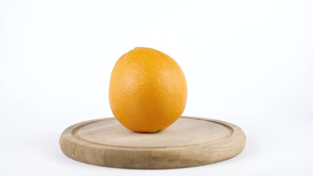 Amount of calories in orange, male hand puts a plate with the number of calories on a orange, healthy nutrition concept 60 fps video
