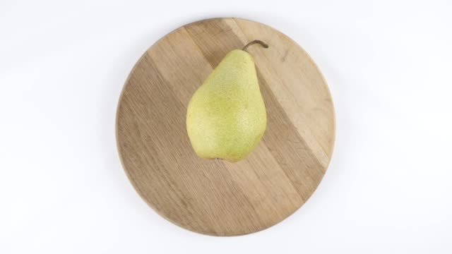 Amount of calories in pear, male hand puts a plate with the number of calories on a pear, top shot 60 fps video