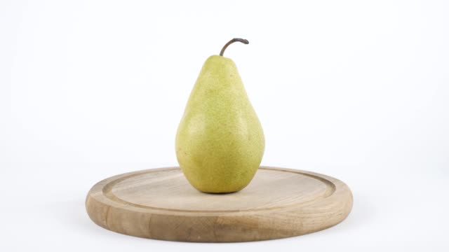 Amount of calories in pear, male hand puts a plate with the number of calories on a pear, healthy nutrition concept 60 fps video