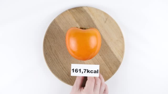 Amount of calories in persimmon, male hand puts a plate with the number of calories on a persimmon, top shot 60 fps video