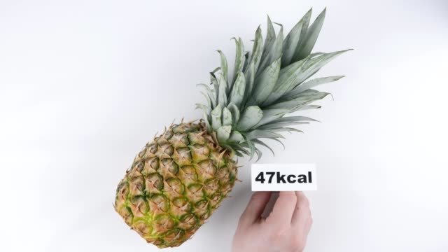 Amount of calories in pineapple, male hand puts a plate with the number of calories on a pineapple, top shot 60 fps video