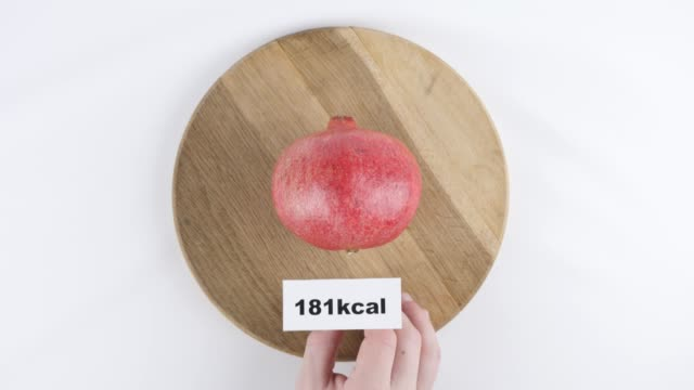 Amount of calories in pomegranate, male hand puts a plate with the number of calories on a pomegranate, top shot 60 fps video