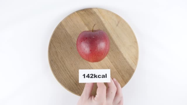 Amount of calories in red apple, male hand puts a plate with the number of calories on a red apple, top shot 60 fps video