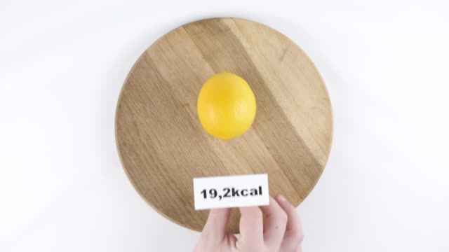 Amount of calories lemon, male hand puts a plate with the number of calories on a lemon, top shot 60 fps video