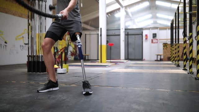 Amputee Athlete Doing Battle Rope Exercises Man With Amputee Leg Doing Battle Rope Exercises In Gym artificial limb stock videos & royalty-free footage