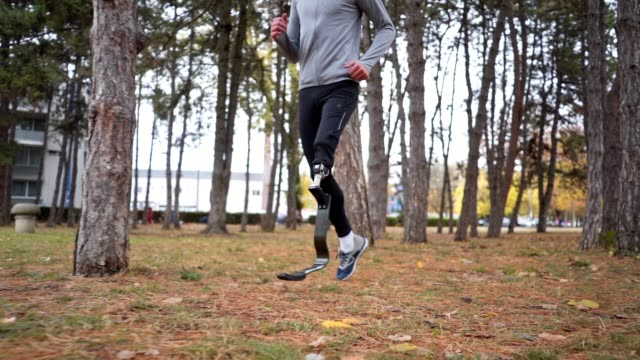 Amputee athlete running in a city forest Young and athletic man with a artificial leg, exercising outdoors, living a healthy lifestyle recovering. artificial limb stock videos & royalty-free footage
