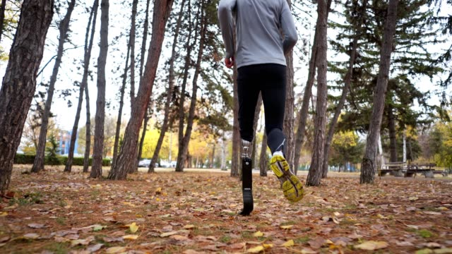 Amputee athlete running outdoors in a forest Young and athletic man with a artificial leg, exercising outdoors, living a healthy lifestyle recovering. artificial limb stock videos & royalty-free footage