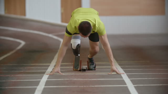 Amputee Athlete Starting Running Young determined amputee athlete with artificial leg starting from blocks and running towards the camera in slow motion prosthetic equipment stock videos & royalty-free footage