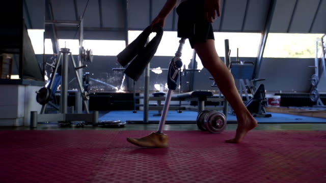 Amputee athlete walking through the gym Amputee athlete with artificial leg, living the healthy lifestyle, exercising in the gym. prosthetic equipment stock videos & royalty-free footage