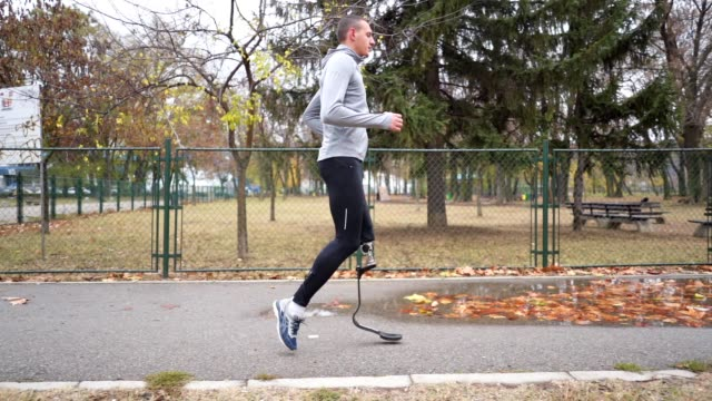 Amputee athlete with a artificial leg running in autumn Young and athletic man with a artificial leg, exercising outdoors, living a healthy lifestyle recovering. artificial limb stock videos & royalty-free footage