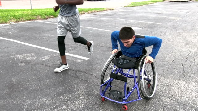 Amputee in wheelchair, friend running beside video