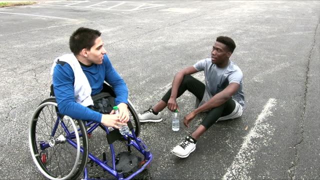 vídeos y material grabado en eventos de stock de paciente en silla de ruedas, cansado del ejercicio, con amigo - deportes en silla de ruedas