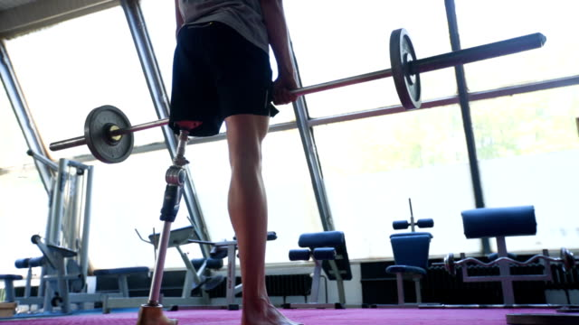 Amputee man doing exercise with barbell Young man with prosthetic leg working out in the gym conquering adversity stock videos & royalty-free footage