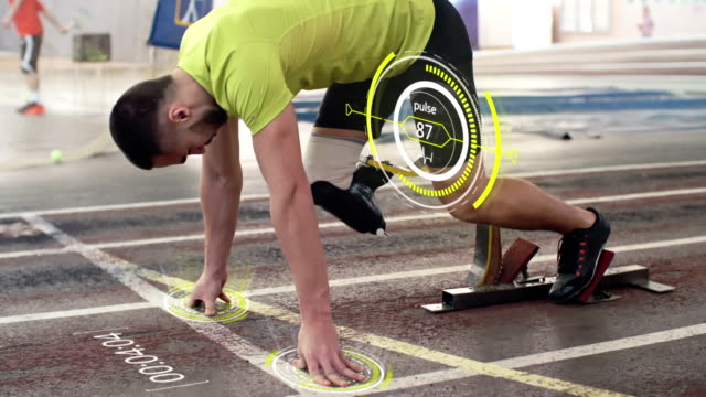 Amputee Man Running on Track with Animated Timer and Pulse Disabled sportsman with prosthetic leg starting from blocks on indoor stadium track and running; pulse projected in the air and digitally animated countdown appearing on track amputee stock videos & royalty-free footage