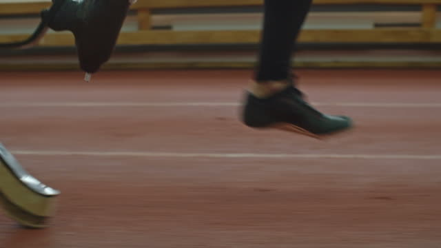 Amputee Sportsman Running on Track Low section of leg and prosthetic limb of amputee athlete accelerating and running on track at indoor stadium artificial limb stock videos & royalty-free footage