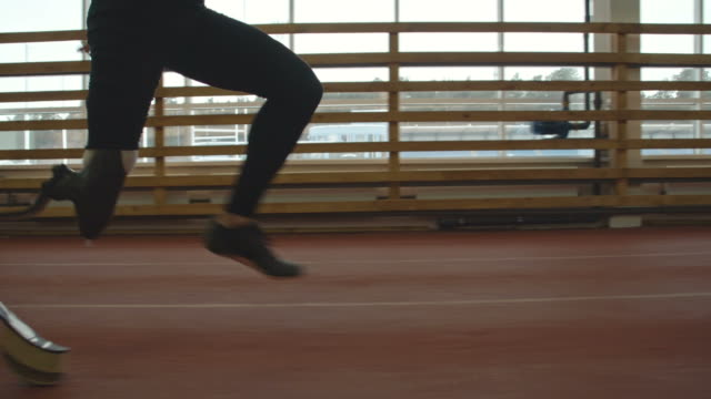 Amputee Sprinter Training Low section tracking of amputee sprinter with prosthetic leg training running on track at indoor stadium artificial limb stock videos & royalty-free footage