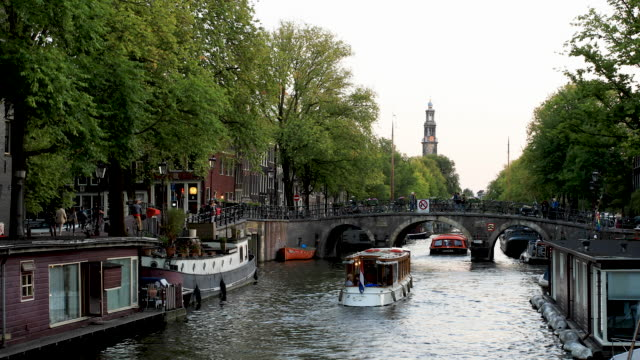 amsterdam canal 4k video with boat traffic on prinsengracht - canale video stock e b–roll