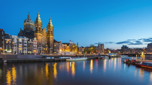 Amsterdam canal and skyline at night with Saint Nicholas Church time lapse in Amsterdam city, Netherlands Amsterdam canal and skyline at night with Saint Nicholas Church time lapse in Amsterdam city, Netherlands amsterdam stock videos & royalty-free footage