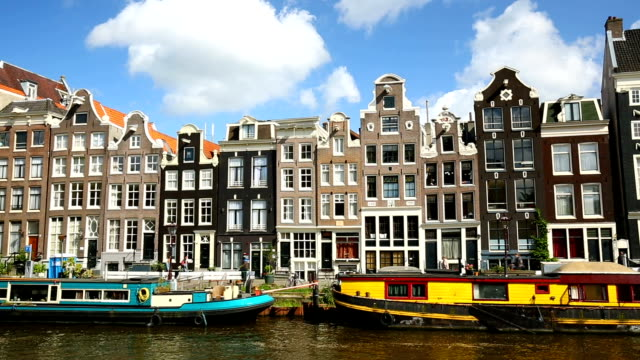 canale di amsterdam con case, panning - amsterdam video stock e b–roll
