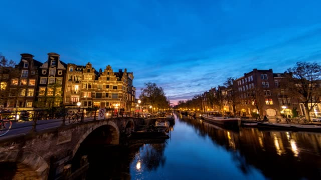 amsterdam city skyline day to night timelapse at canal waterfront, amsterdam, netherlands, 4k time lapse - amsterdam video stock e b–roll