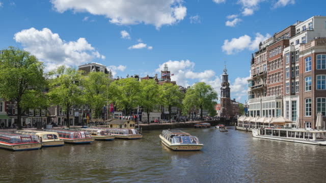 amsterdam city skyline with canal and boat in amsterdam city, netherlands time lapse - amsterdam video stock e b–roll