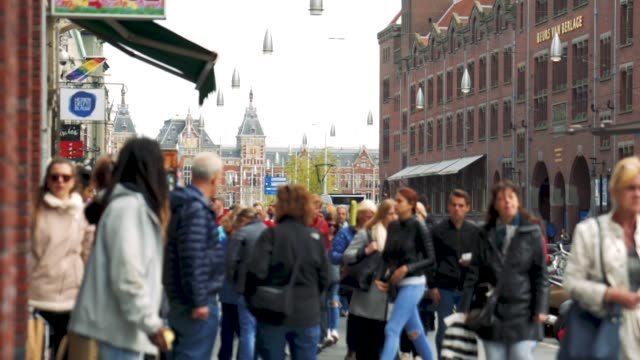 Amsterdam Damrak & Central Station Slow-motion shots of people walking and cycling on the Damrak in Amsterdam with Central Station in the background. netherlands stock videos & royalty-free footage