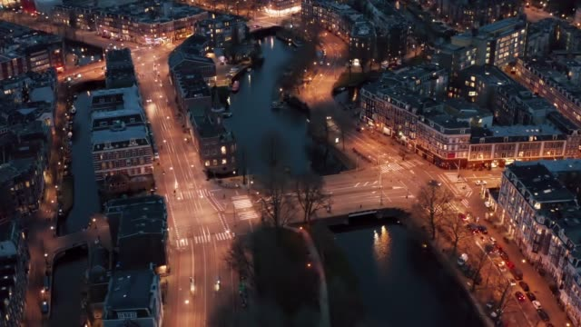 Amsterdam Netherlands aerial view at night. Old dancing houses, river Amstel, canals with bridges, old european city landscape from above