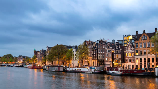 amsterdam netherlands time lapse 4k, city skyline day to night timelapse at canal waterfront - amsterdam video stock e b–roll