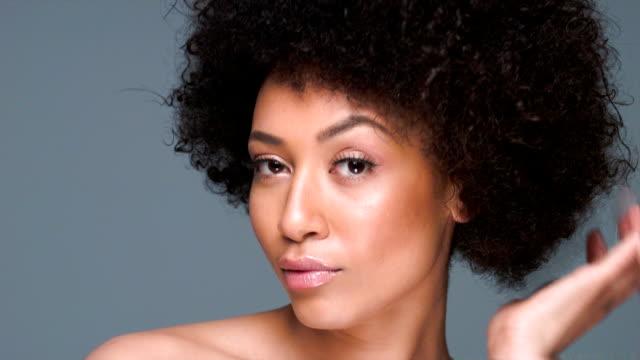 vidéos et rushes de amusé femme afro-américaine se peigner ses cheveux - soins capillaires