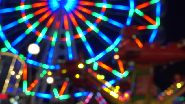 Amusement park at night, ferris wheel and carousel.