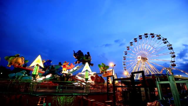 nöjesparken på twilight time med pariserhjul - fritidsanläggning bildbanksvideor och videomaterial från bakom kulisserna